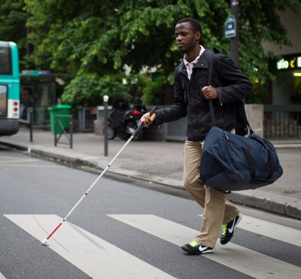 blind man with cane crossing busy city street